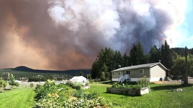 Un panache de fumée s'élève de derrière une maison.