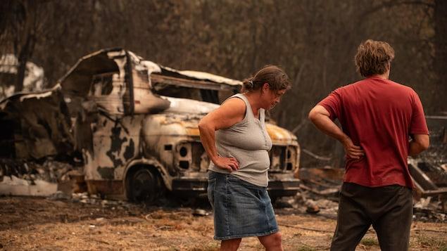 Un homme et une femme sont debout devant une camionnette calcinée dans le village de Monte Lake.