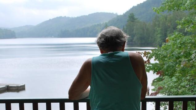 Un homme regarde un lac à partir d'un balcon.