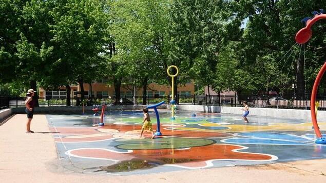 Deux garçonnets jouent dans les jeux d'eau d'un parc sous l'oeil attentif d'une femme.