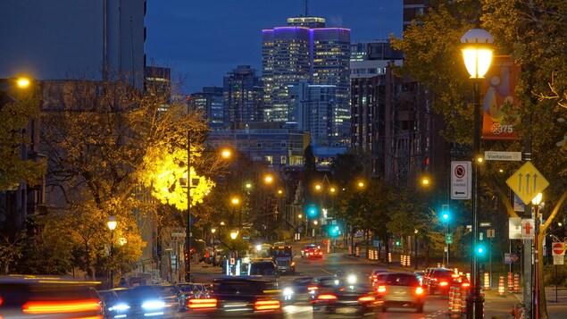 Des voitures circulent sur la route, alors que le jour se lève sur le centre-ville de Montréal.