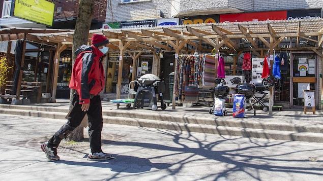 Un homme marche dans rue commerçante. Seul un quincaillier est ouvert.