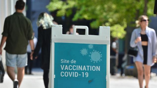 Des passants près d'un centre de vaccination contre la COVID-219 à Montréal.