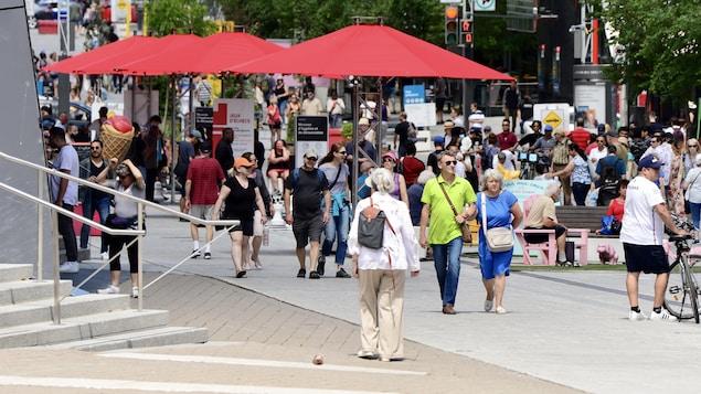 Des gens déambulent sans masque à la Place des Arts, à Montréal.