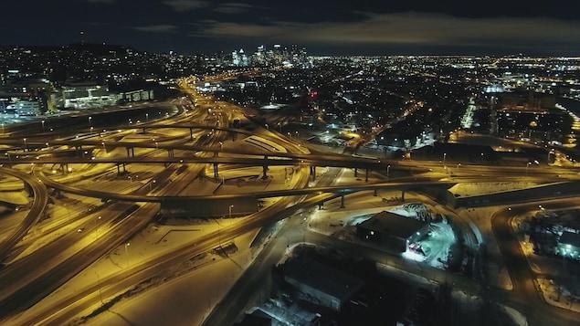 Une vue aérienne et de nuit de l'échangeur Turcot, avec au fond le centre-ville de Montréal.
