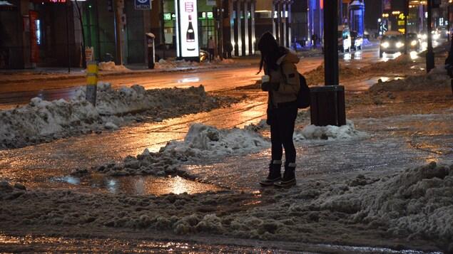 Une piétonne dans une rue verglacée.