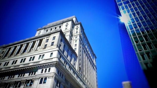 Le soleil se reflète sur les fenêtres d'un immeuble à plusieurs étages lors d'une journée d'été ou le ciel est complètement dégagé.