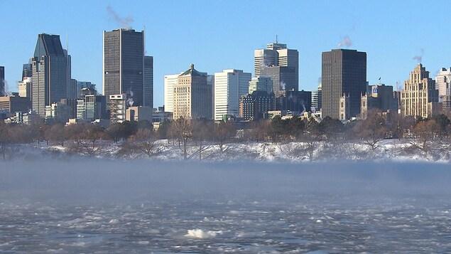 De la fumée s'échappe du fleuve Saint-Laurent avec des immeubles montréalais en arrière-plan.
