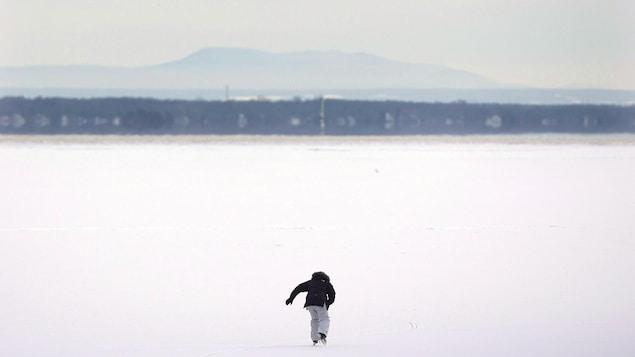 Un homme fait du patin à Lac-Saint-Louis, dans l'ouest de Montréal.