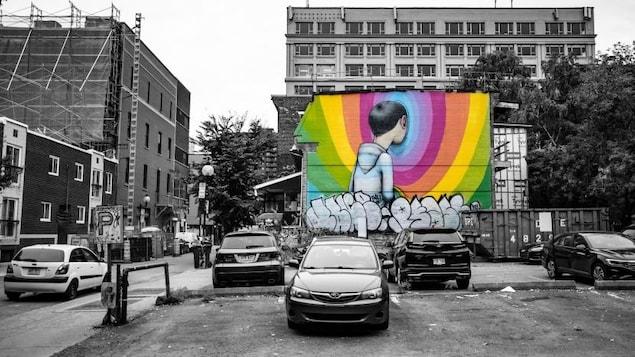 Une photo de la ville en noir et blanc avec une murale en couleur d'un homme tourné vers le mur.