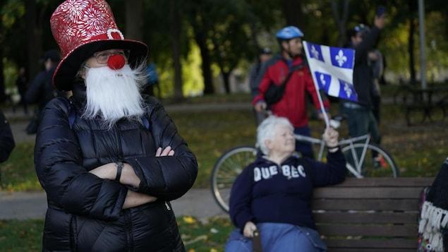 Une femme qui porte une barbe blanche et un nez de clown se tient dans le parc.
