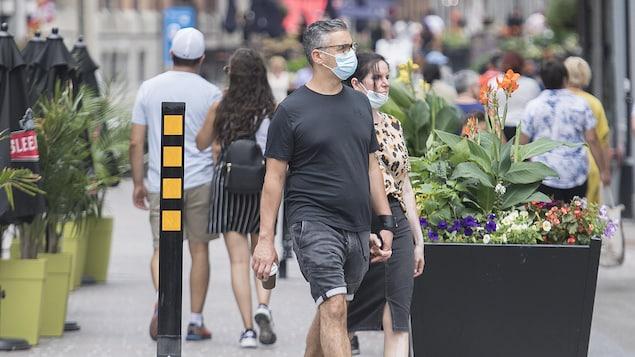 Un couple marche dans une rue piétonne.