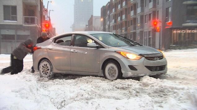 Trois hommes, un au volant  et deux autres poussent un véhicule enlisé dans la neige.