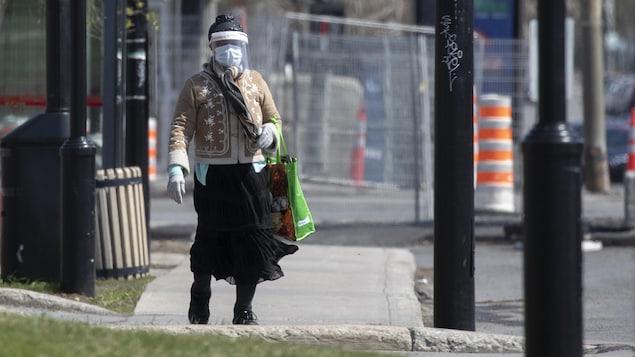Une femme masquée marche sur un trottoir de l'arrondissement de Montréal-Nord.