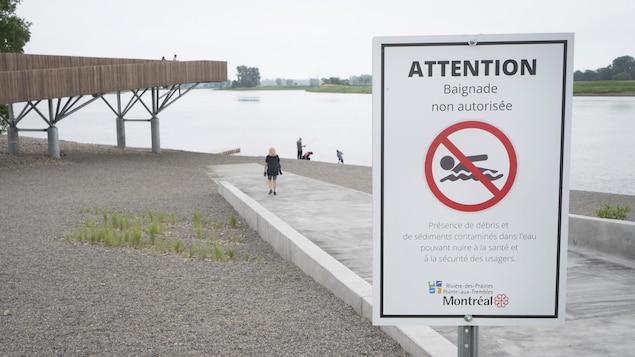 Quelques personnes sur le bord du fleuve, près d'une affiche d'interdiction de baignade.