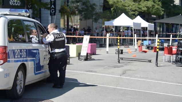 Un policier du SPVM accoudé à une fourgonnette de la police.
