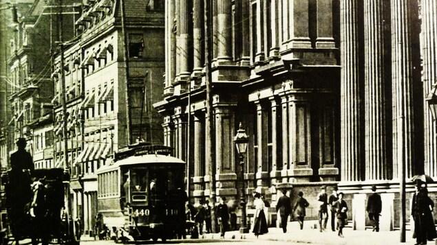 Photo d'archives montrant une rue de Montréal en 1890 avec un tramway, une calèche tirée par un cheval et des passants sur un trottoir devant d'imposantes façades