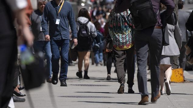 Des gens marchent sur un trottoir du centre-ville de Montréal.