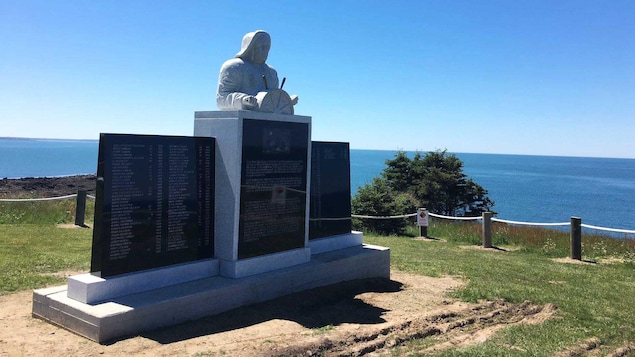 Gros plan sur le monument, sur une falaise, avec vue sur l'océan. Un capitaine de bateau tient la barre d'un navire au centre du monument. La sculpture est de l'artiste Marc Graff.
