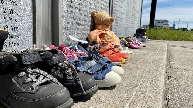 Des chaussures et un ours en peluche sont au pied du monument dédié aux enfants du pensionnat pour Autochtones à Fort Providence.