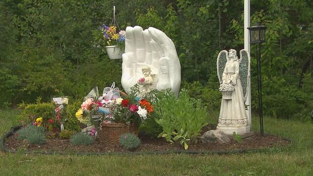 Un monument commémoratif et des statues se trouvent au milieu de fleurs et de plantes.