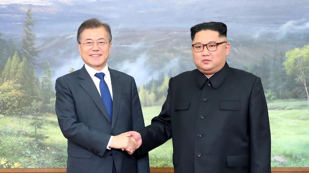 Les deux hommes se tiennent côte-à-côte, Moon Jae-in à gauche, et Kim Jong-un à droite.
