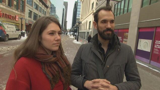 Une femme et un homme vêtus de manteaux sont en entrevue  à l'extérieur, sur une rue.