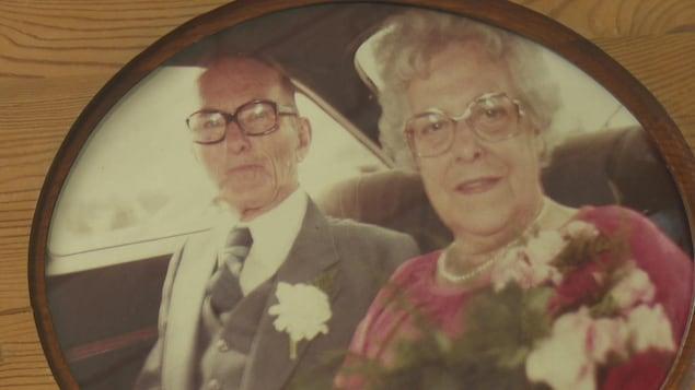 Un couple habillé chic, portant boutonnière et fleurs de corsage, assis sur la banquette arrière d'un véhicule.