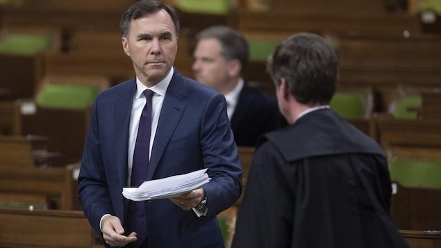 Bill Morneau remet une pile de documents à un employé des Communes.
