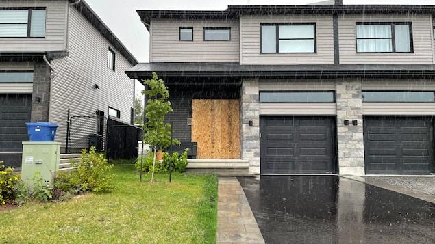 Photo de la résidence semi-détachée. La porte d'entrée a été recouverte de planches de bois compressé.