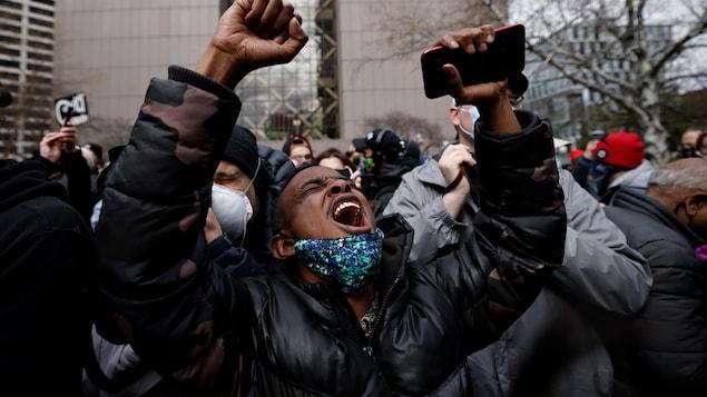 Un jeune homme noir lève ses bras vers le ciel en criant.