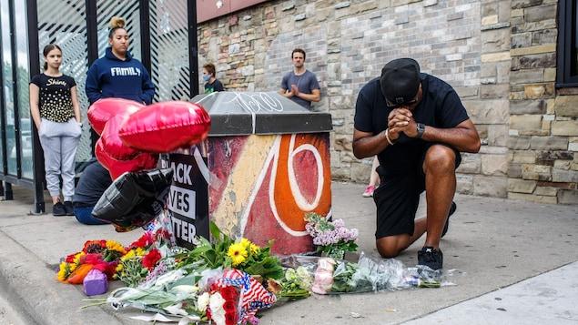 Un homme à genoux fait une prière près du mémorial, sur lequel on peut lire : « Black Lives Matter » (La vie des Noirs compte).