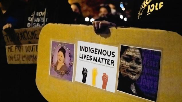 Une personne tient entre les mains une pancarte sur laquelle est écrit en anglais « indigenous lives matter ».