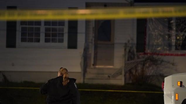 Un ruban de police jaune devant une résidence durant la nuit et une policière de dos, montant la garde.