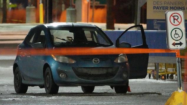 La petite voiture est derrière un ruban de police, une portière ouverte.