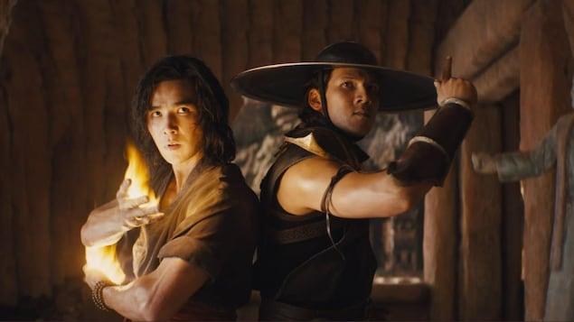 Deux combattants de l'univers Mortal Kombat côte à côte dans un décor intérieur rustique.