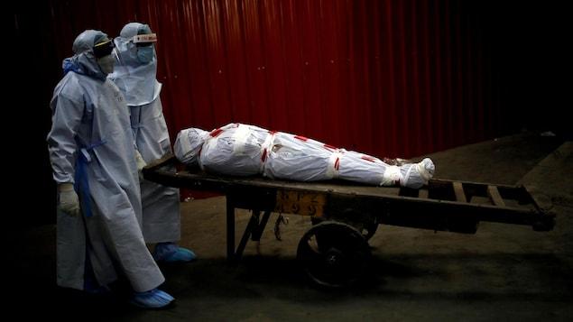 Un cadavre emmailloté poussé par deux personnes en tenue de protection.