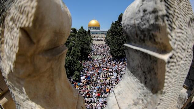 Une foule en prière près d'un dôme doré.