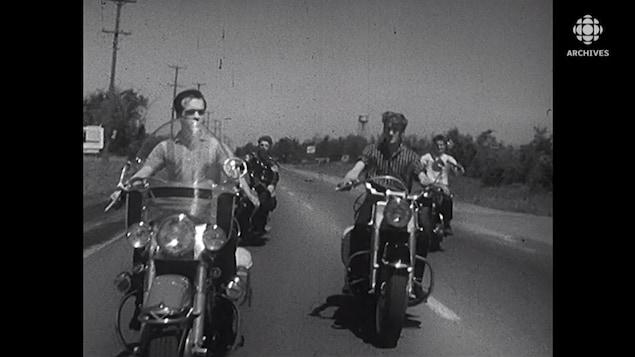 Jeunes hommes qui font de la moto.