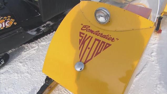 Une petite motoneige antique de couleur jaune est garée à proximité d'un sentier.