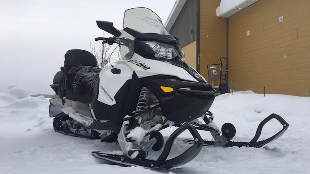 Une motoneige Ski Doo est stationnée près d'un bâtiment.