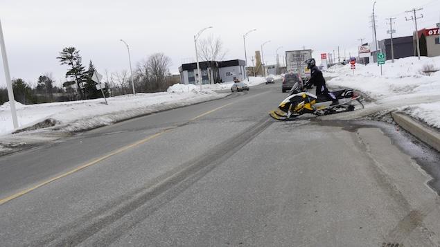Un motoneigiste s'apprête a traverser la route.