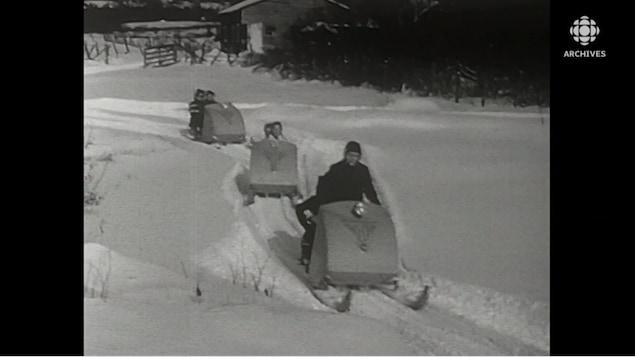 Groupe de motoneigistes sur un sentier.