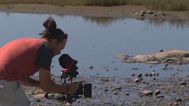 Sébastien Rioux en train de filmer un beau paysage de la MRC des Basques.