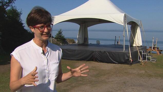 Karine Vincent accorde une entrevue à Radio-Canada devant une scène extérieure près de l'eau.