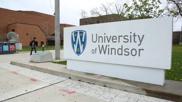 Un panneau de l'Université de Windsor avec un étudiant qui marche au loin.