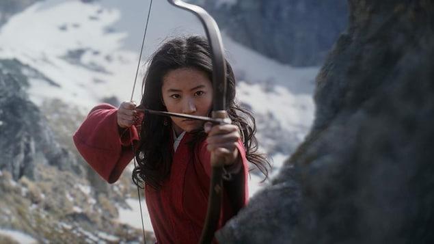 Une femme vêtue d'une tenue rouge tend la corde d'un arc à flèche.