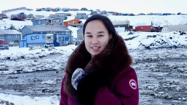 Mumilaaq Qaqqaq porte un manteau rouge. En arrière-plan, la capitale du Nunavut, Iqaluit.