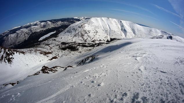Des pistes de ski au sommet de la montagne enneigée.
