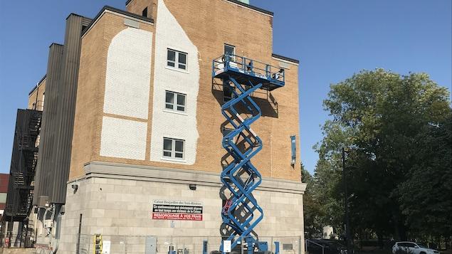 Une partie du mur extérieur du bâtiment qui abrite la caisse Desjardins est recouverte de peinture blanche.